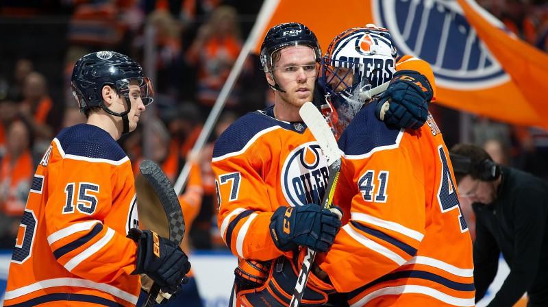 """Konors Makdeivids (centrā) apsveicot vārtsargu Maiku Smitu viņa pirmajā uzvarā Edmontonas """"Oilers"""" kreklā. Foto: Codie McLachlan/AFP/Scanpix"""
