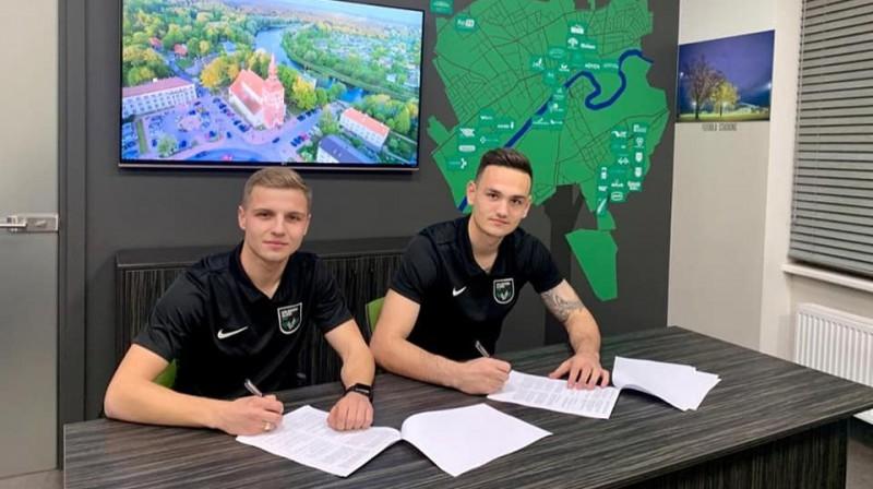 Mikola Musolitins (no kreisās) un Andrijs Kožuhars paraksta līgumus. Foto: Valmiera Glass/ViA
